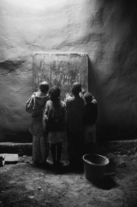 Underneath a street lamp, children study math in Sikasso, Mali late at night.
