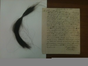 The lock of hair and letter of reference for George Ransom included in the back of Sherwood Ransom's whaling journal.