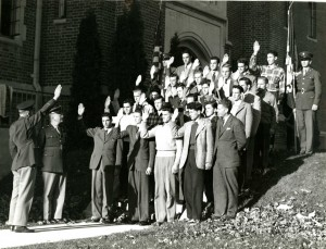 A group of students are inducted into the Army Air Corps Reserve by Captain Raymond Flint in front of Wood Hall, October 1942.