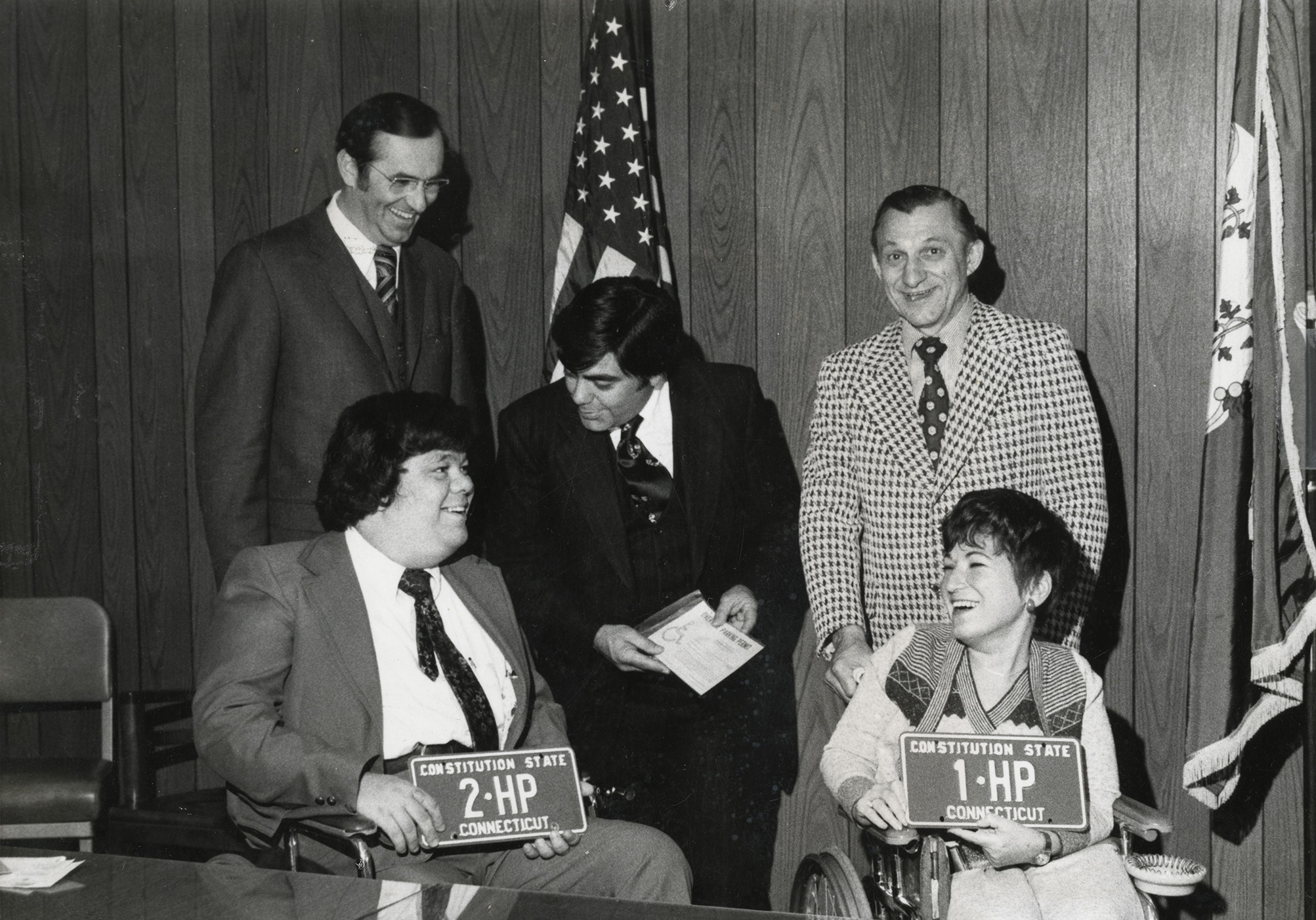 -	Phyllis Zlotnick (bottom right) photographed holding Connecticut's first state license plate for handicapped residents