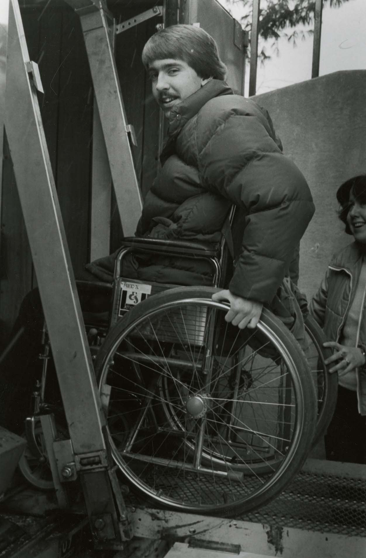 UConn student in a wheelchair loading into a transport van on the Storrs campus, 1981