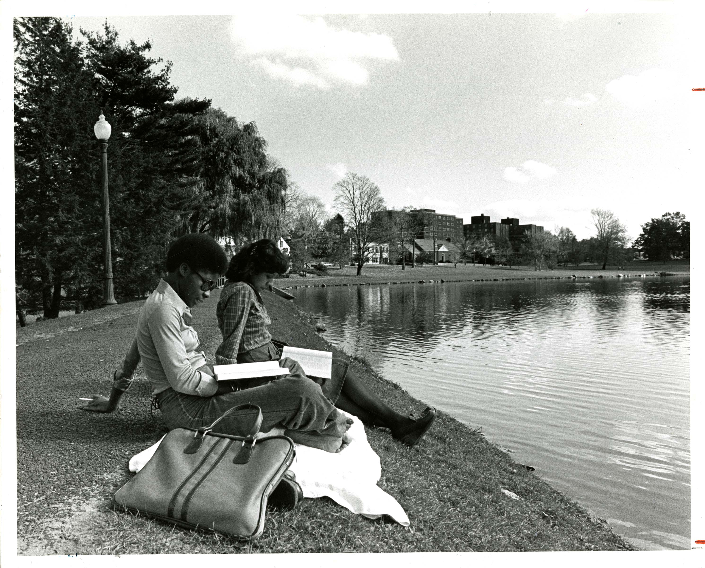 UConn students reading by Mirror Lake, 1977