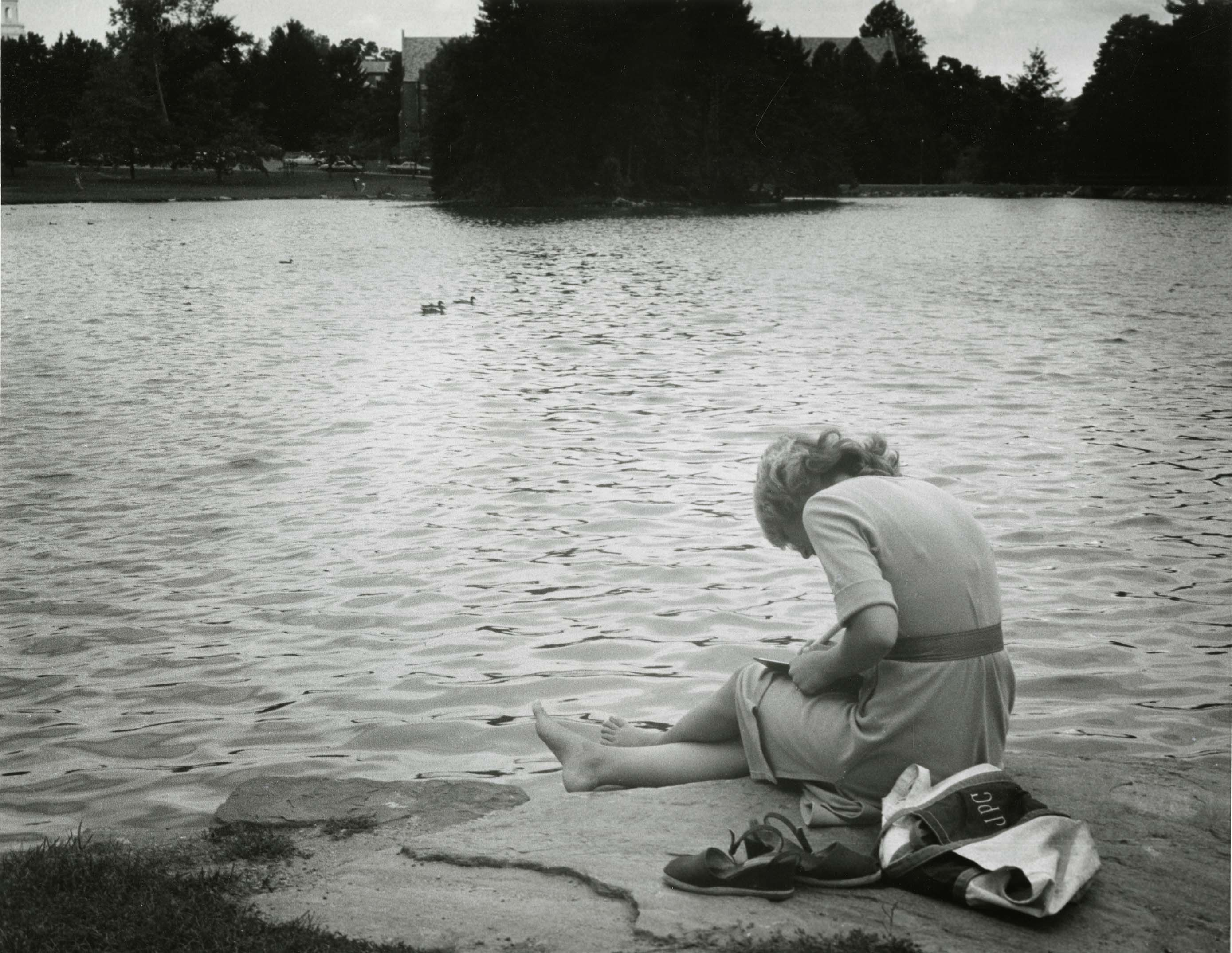 UConn student reading next to Mirror Lake, 1980