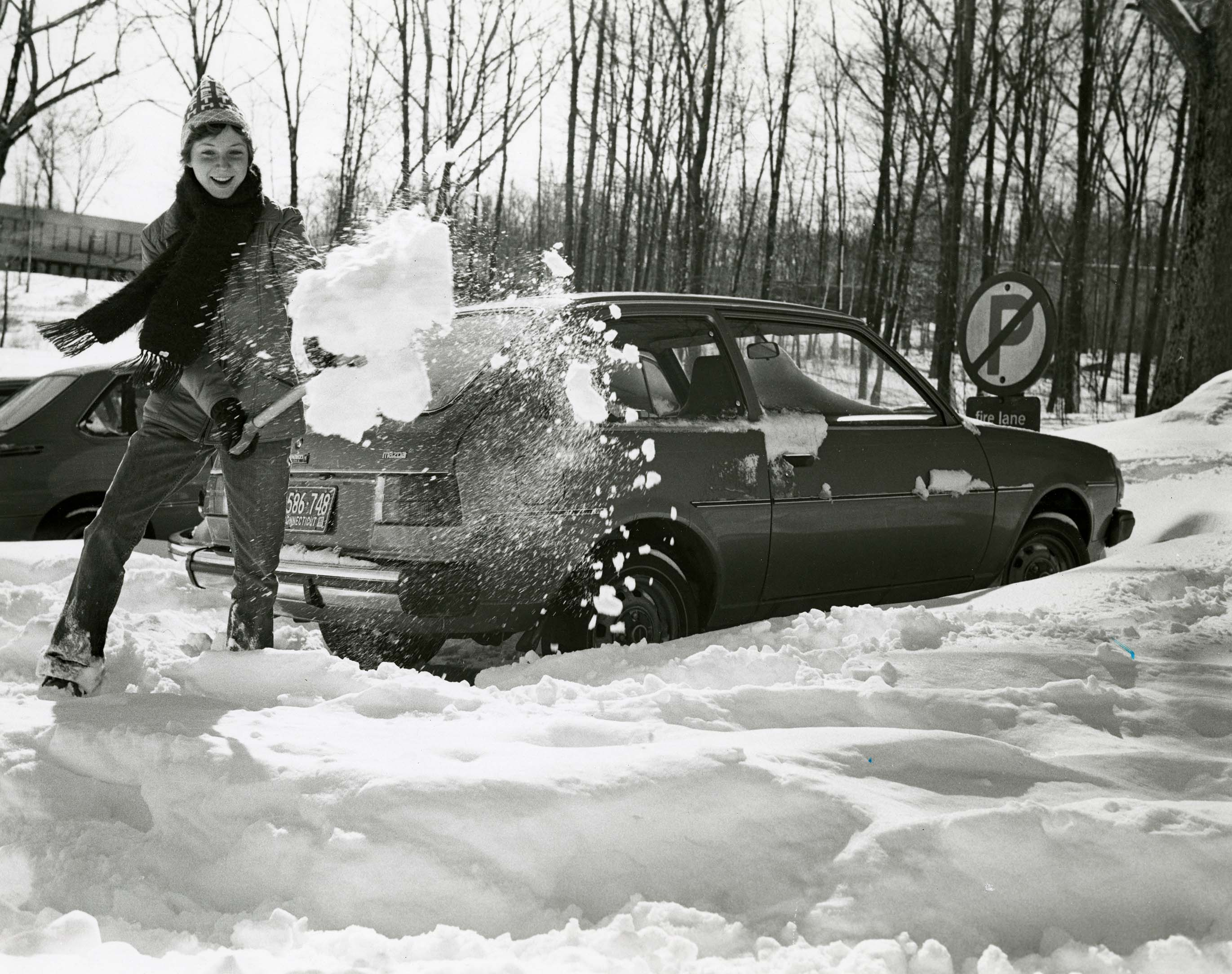 UConn student shoveling snow on the Storrs campus, 1978
