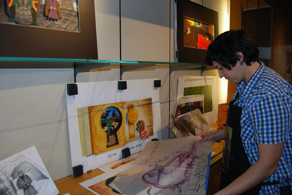 "Professor Alison Paul installs her exhibit featuring art from her children's book ""The Crow."""