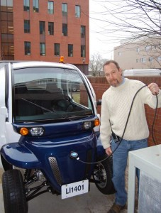"The Libraries' David Avery takes a moment to ""fuel"" the new vehicle in an outlet at the loading dock."
