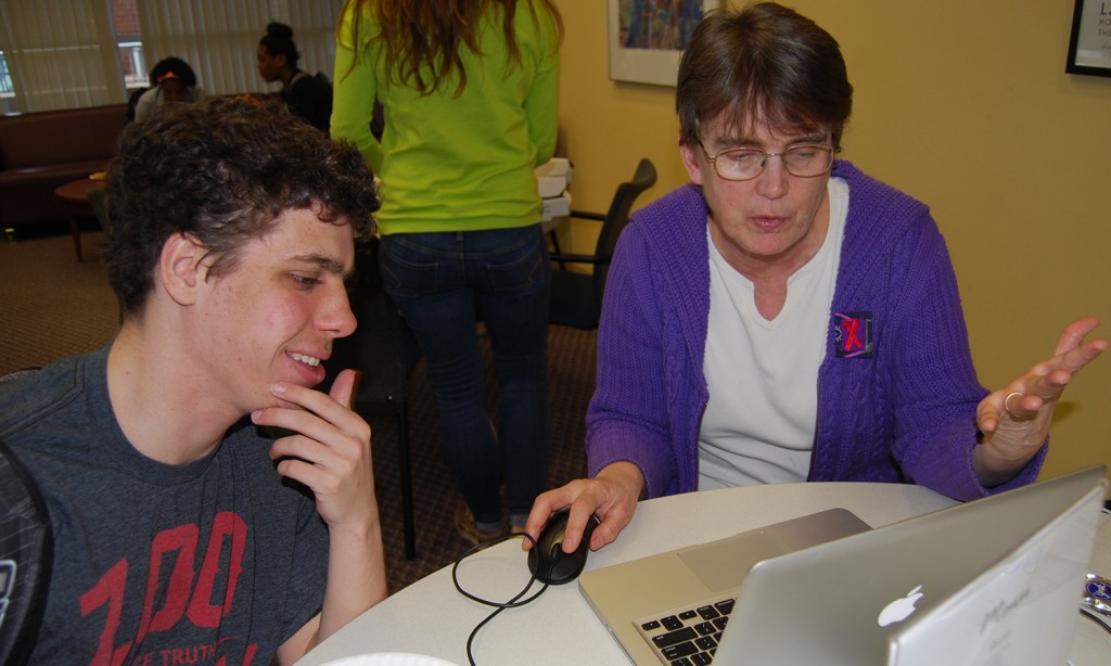 Subject Specialist Kathy Labadorf assists a student with his assignment.