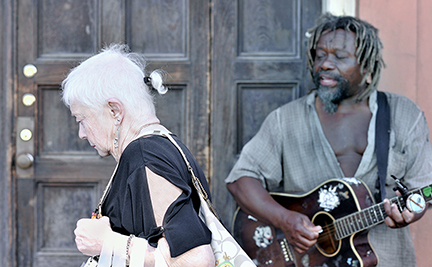 A tourist passes by homeless guitarist in New Orleans