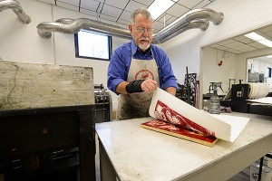 Gus Mazzocca, professor emeritus of art and art history makes a print at the new printmaking facility at the Bishop Center.