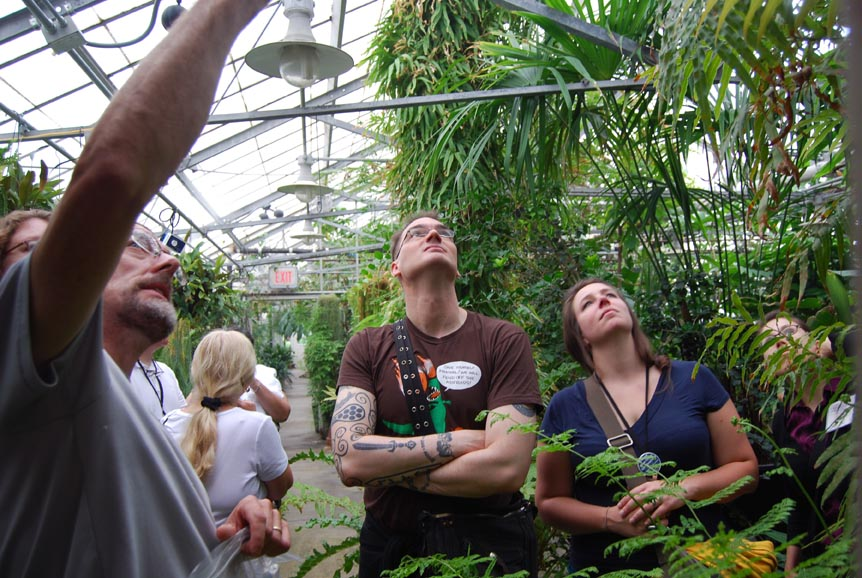 Scott Martin from the University of Michigan and Lauren Olewnik from Castleton State College listen to Clinton Morse's description of a plant in the greenhouse.